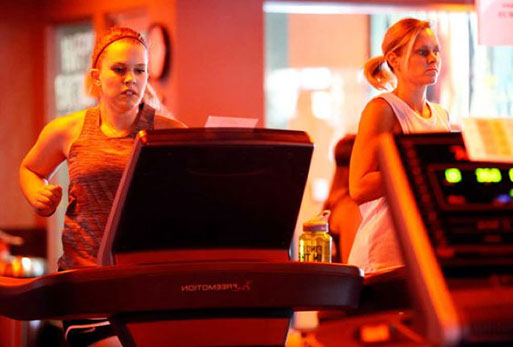 Two Orange Theory Fitness members running on a treadmill