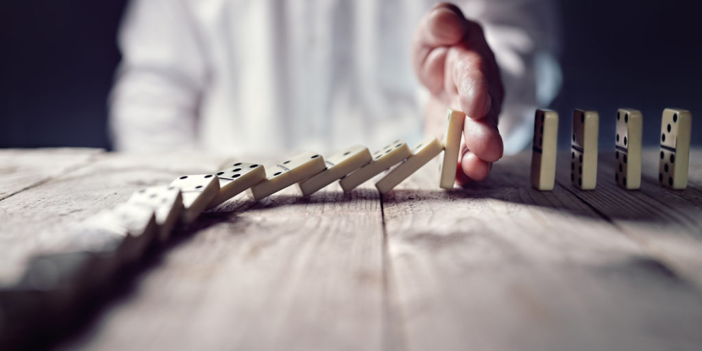 A person stopping the domino effect