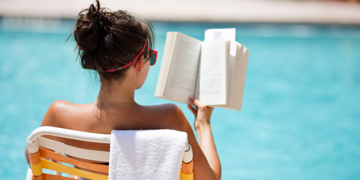 Woman sitting beside a swimming pool and reading a book